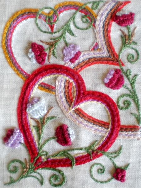 Layered hearts / flowers in what looks like wool threads (chain stitch & various)