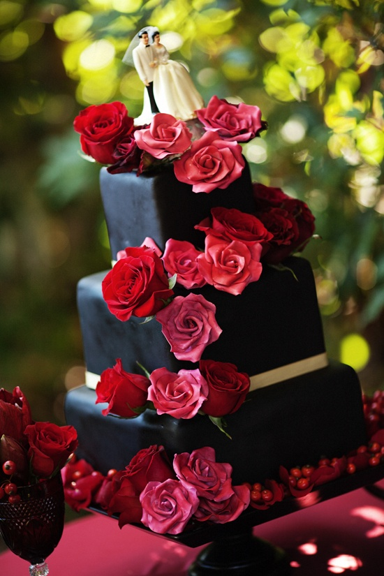 Decadent, elegant black cake with red roses and gold trim. Ooh la