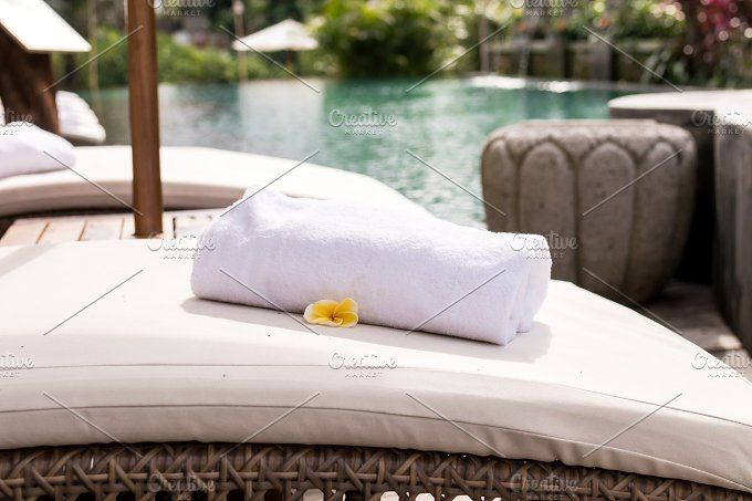 Close up of towel with plumeria frangipani on deck chair at resort pool. Bali island, Indonesia. Photos Close up of towels on deck chair at resort pool by Belart84