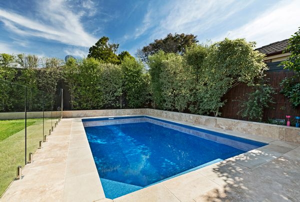 Built by Albatross Pools, this rectangular pool is 7.0m x 4.0m in size and is complete with four deck jets running alongside the pool's edge. Featuring the premium metallic Costa Rica Aqualux pool interior, the pool is surround by Travertine Tiles and Glass Pool Fencing.