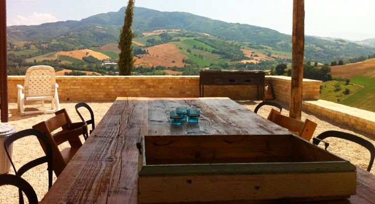 A covered terrace with a bbq and a large dining table with beautiful views over the hills towards the Sibillini mountains.