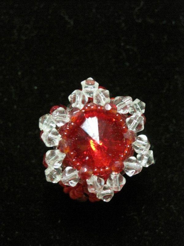 Anello con rivoli di colore rosso, biconi in vetro trasparente e conteria di colore rosso.
