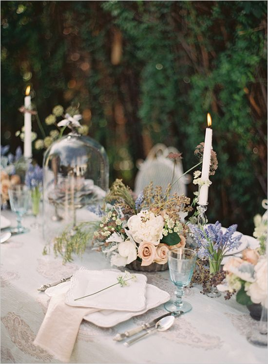 Taper candles, bell jar over herbs, nice glasses, blush flowers and greenery.