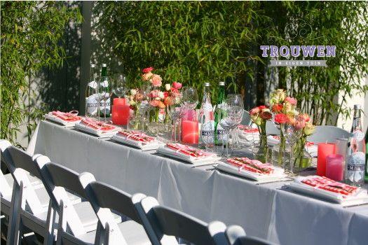 Witte klapstoelen, wit linnen en fleurige accenten in de kleuren koraal, wit en roze. www.trouwenineigentuin.nl