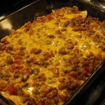 Easy Taco Casserole Recipe 1 pound lean ground beef 1 can Ranch Style beans 1 10-12 ounce bag tortilla chips, crushed 1 can Ro-tel tomatoes 1 small onion, chopped 2 cups shredded cheddar cheese, divided 1 package taco seasoning 1 can cream of chicken soup 1/2 cup water sour cream and salsa for serving