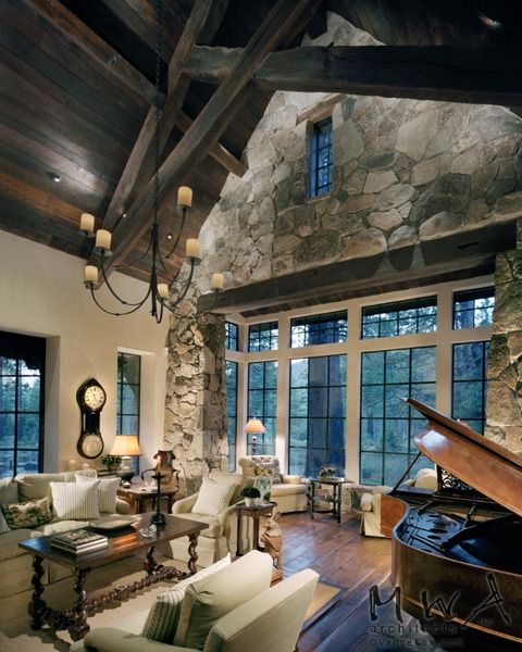 Dark grey-brown stain on exposed trusses/purlins with wood ceiling. Trim-less doors and windows. Stone is used as an interior finish.