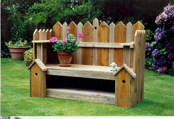 .Garden bench with birdhouses made from old fencing wood. t