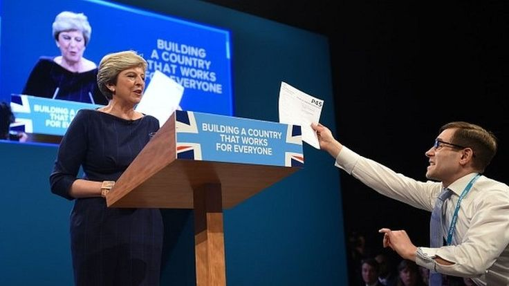 """Theresa May battles a sore throat and being interrupted by a prankster to set out her vision for a """"compassionate modern Britain""""."""