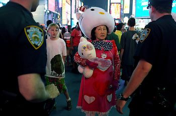 Photography By Zack Arias http://beam.zackarias.com/: I was drawn to this image as a result of its humorous quality. The subject dressed in a Hello Kitty costume is perfectly framed by the two menacing police officers, their dark uniforms contrasting her bright red outfit. I was also attracted to the cool neon lights gleaming in the background of the frame.