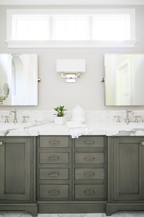 A gray dual washstand adorning bronze pulls and a statuary marble countertop is fitted with his and her sinks with polished nickel hook and spout faucets fixed in front of a statuary marble backsplash positioned beneath rectangular pivot mirrors.