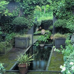 Water running into a mirror makes this garden looks like it goes on beyond the fence - clever!