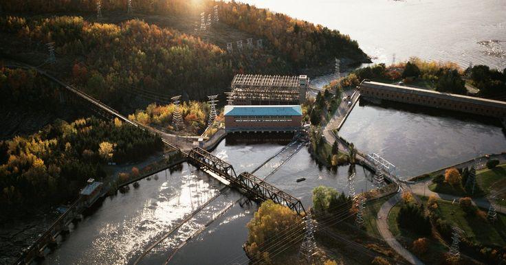 Ventajas y desventajas de usar energía hidroeléctrica. Las plantas hidroeléctricas pueden generar electricidad desde el fluir del agua de un río o la liberación de la misma desde un embalse. El agua puede hacer girar un molino, turbina u otro dispositivo, el cual convierte la energía cinética del agua corriente en energía eléctrica. Las plantas de energía hidroeléctrica a menudo incluyen una represa ...
