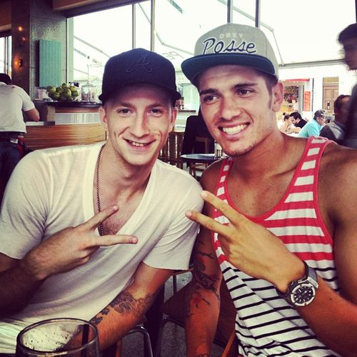 Marco Reus and Roman Neustädter sporting snapbacks, plunging necklines and tattoos