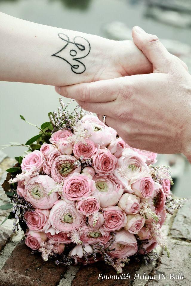 Svatební kytice je uvázána z ranunculusu, růže, limonium.