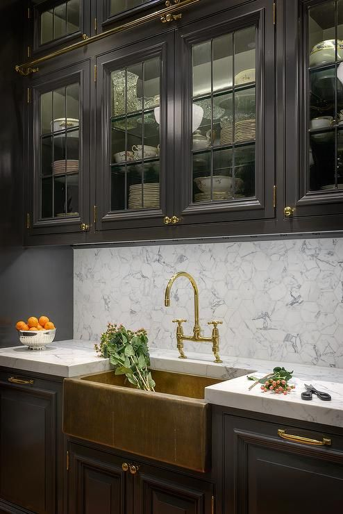 Black galley kitchen features glass front upper cabinets fitted with a brass ladder rail and black lower cabinets adorned with brass hardware paired with gray and white marble countertops and backsplash.