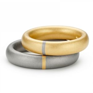 "Niessing Tecum. ""A part of me will always be with you, forever ""at your side"". One segment of the wedding ring has a different color or is made of a different material than the rest of the ring. This segment always relates to the partner's ring."