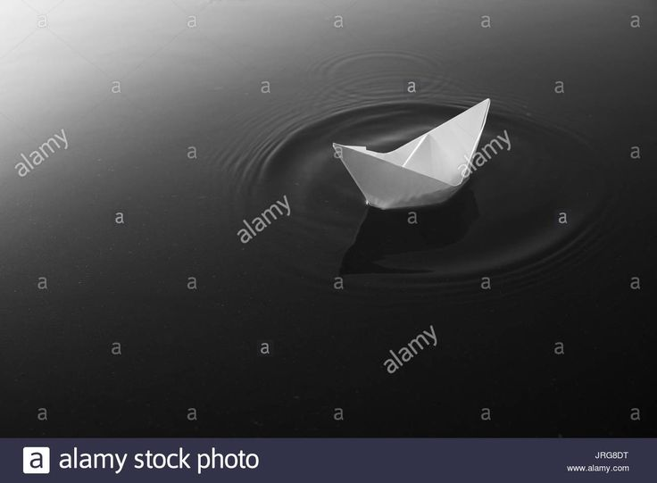 Download this stock image: Paper boat floating on calm lake waters. Monochrome - JRG8DT from Alamy's library of millions of high resolution stock photos, illustrations and vectors.
