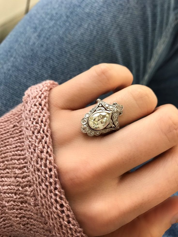 The Lucy ring is an Edwardian Engagement Ring circa 1910! This rare beauty centers an old Pear cut diamond weighing approximately 2.32 carats of M-N color, SI1 clarity. The diamond is held in a platinum bezel setting that is surrounded by 24 additional diamonds that are artfully arranged to create a one-of-a-kind look! The setting has subtle millegrain throughout. The ring is size 6 and can be resized!