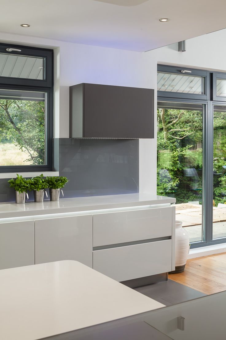 A Highly Contemporary Crisp Handleless Gloss Lacquered White Kitchen With  Matt Grey Accents. Corian Worktops With A Designer Illuminated Fin At One  End Of ...