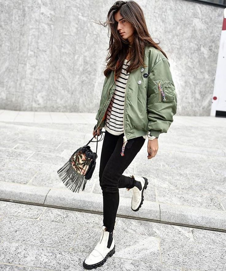 Striped tee, bomber jacket, black jeans, white boots.
