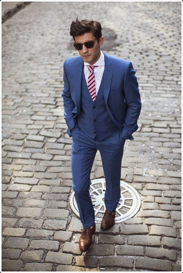 A red and white striped tie goes perfectly with the blue suit.