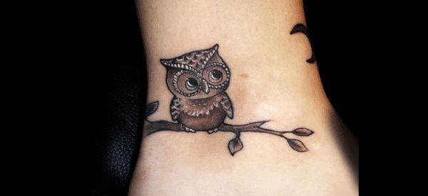 tatuaje de buho en la muñeca