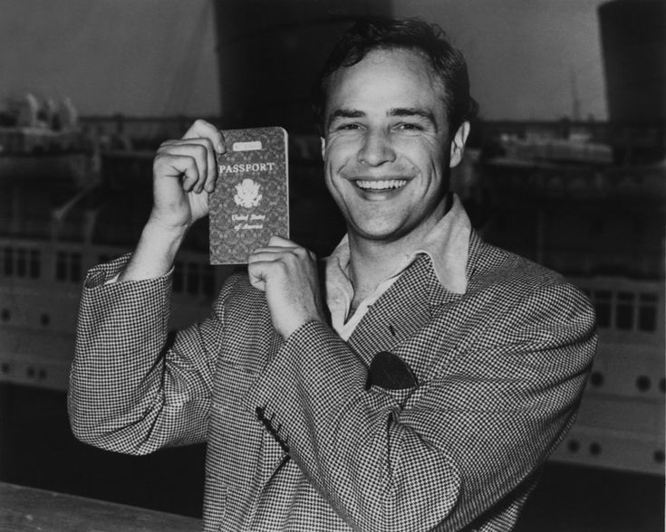 Marlon Brando proudly displaying his US passport before heading to Europe.   21 Candid Photos Of Old Hollywood Celebs