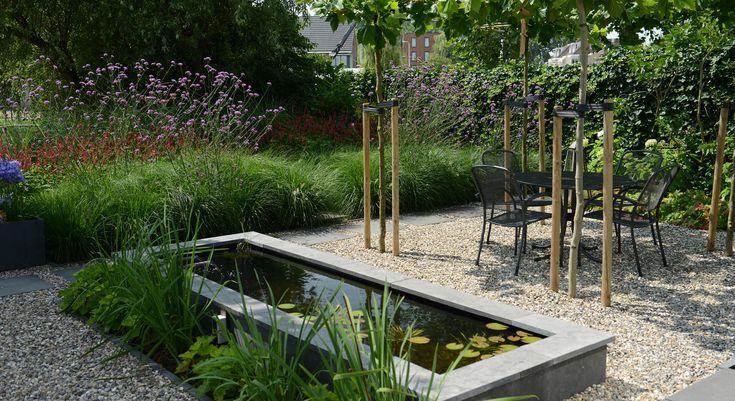 Rodenburg tuinen: achtertuin met hoogteverschil, inclusief een decoratief element in de vorm van een spiegelvijver. Deze tuin met veel groen biedt meerdere zitplekken. Het grind en de staptegels maken de tuin nog levendiger.