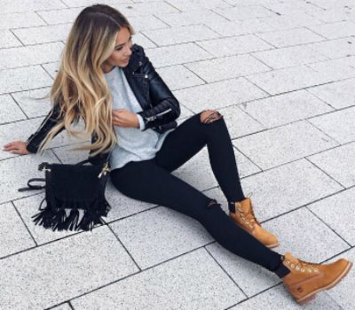 Janine Wiggert + classic sandy brown Timberlands + black jeans + blue sweater + leather jacket + leather + frayed suede cross-body bag.  Bag: Camelia Roma, Shoes: Timberland.