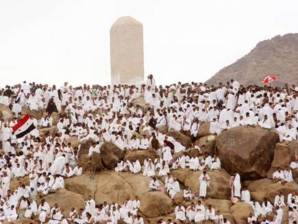 Mountain on the plain of Arafat where dozens of people dressed in white sit in contemplation and prayer. Arafat is the most important part of the Hajj