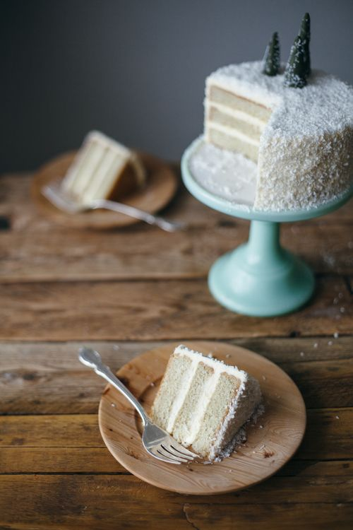 Snowy-looking coconut layer cake topped with a trio of tiny Christmas trees