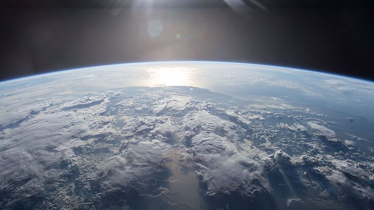 The Sun's light is reflected off a body of water as the space station orbit's Earth.