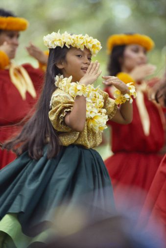 Stock Photo : Hawaii, Oahu, Keiki Hula, view of young girl with plumeria lei and haku, hands in front  of face, women in background