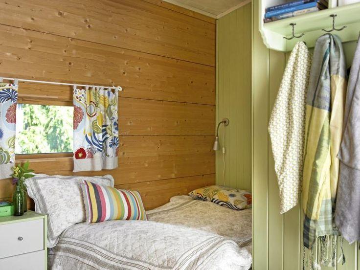 Her strekker sengen seg fra vegg til vegg og skaper en koselig liten sovekrok. Den ene veggen har blitt malt i en lys pastellgrønn tone, mens den andre har fått beholde sin naturlige trefarge.