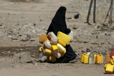 World Water Day 2016 A woman carries jerry cans to fill them with water from a communal tap in Yemen's capital SanaaReuters