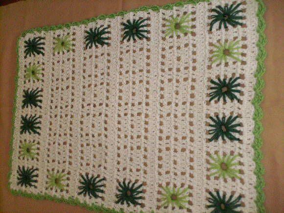 Tapete de barbante retangular na cor cru com bordado verde escuro e verde claro.