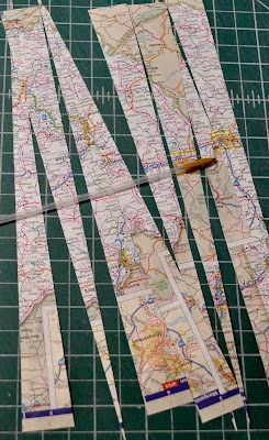 Paper Map Beads, the author made a clever rolling tool from the tubing of an old pen.