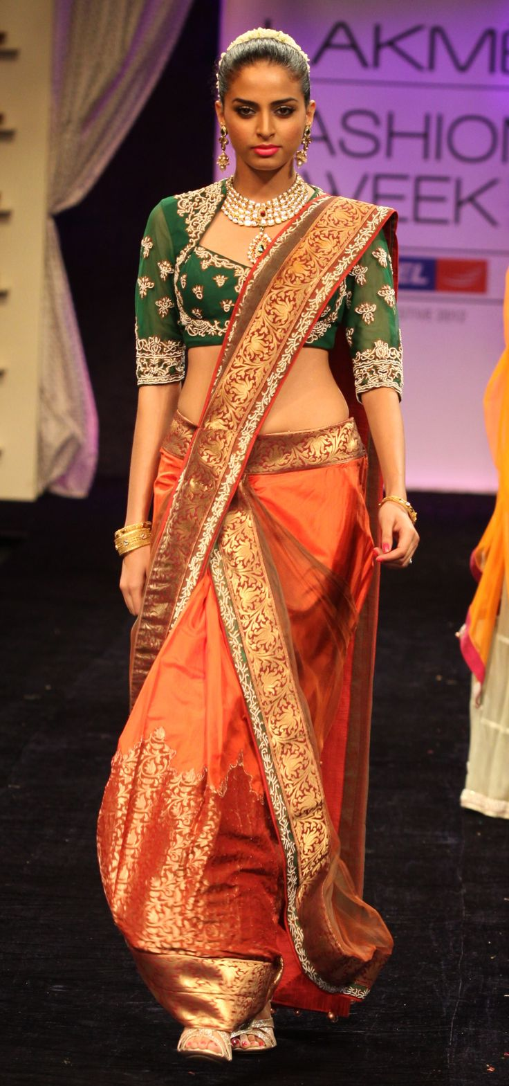 Orange draped saree with green embroidered blouse.