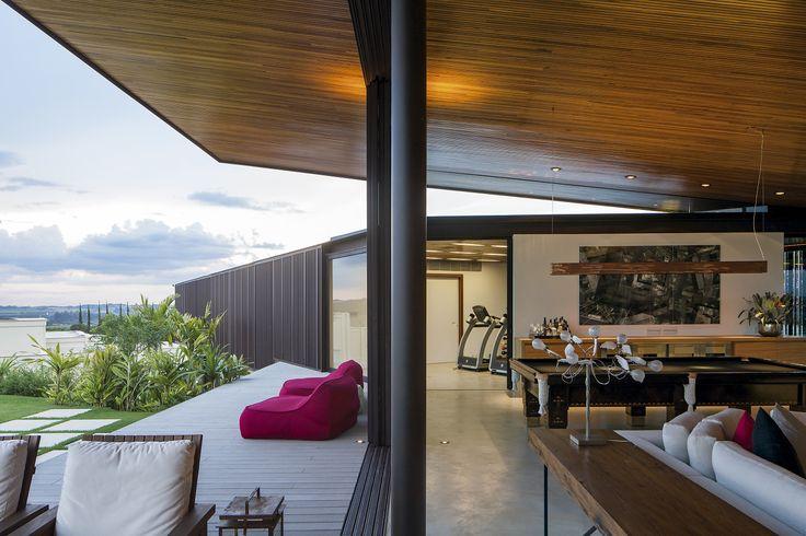 Os ângulos não ortogonais desta casa permitiram orientar a área social, transparente e com uma cobertura leve e inclinada em madeira, para a vista.