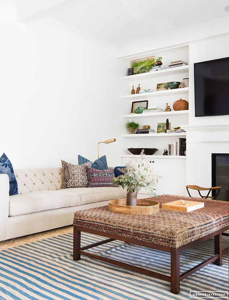 Such great details in this space - upholstered coffee table, pillow mix,  striped rug - 25+ Best Ideas About Upholstered Coffee Tables On Pinterest