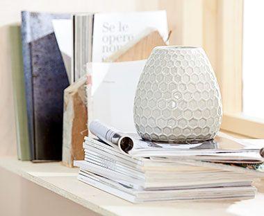 Vindueskarm indrettet med grå vase og magasiner