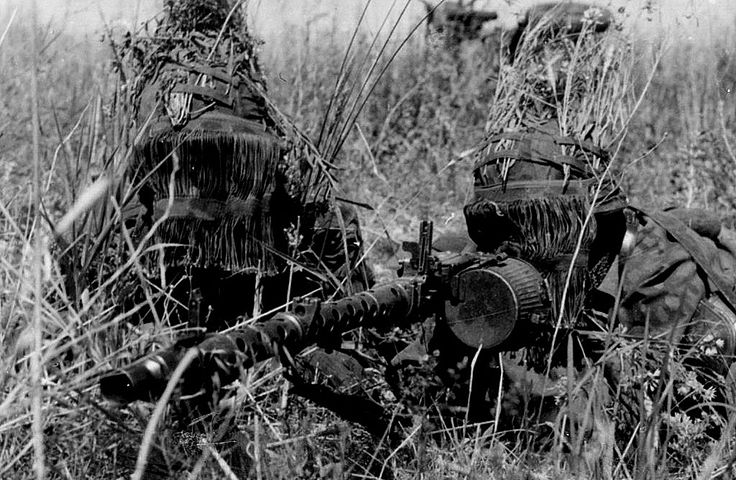 "Caption: ""Looking like creatures from a science-fiction movie, a Totenkopf Division MG 34 team with face masks and extensive foliage tied on to their helmets during the Battle of Kursk, summer 1943."""