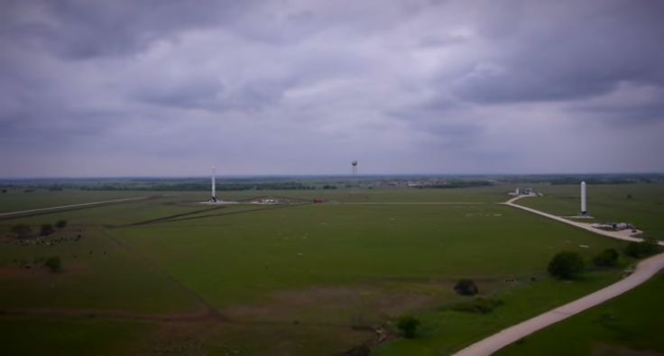 A SpaceX Falcon 9 Reusable rocket prototype (left) and the firm's smaller Grasshopper test bed (far right) are seen atop their test pads in McGregor, Texas. This still image was taken from an aerial drone video released by SpaceX on April 18, 2014. Original Image Credit: SpaceX