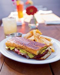 """Mojo Pork Cubanos - Roy Choi's outstanding sandwich features slices of garlicky roast pork layered with grilled boiled ham (""""American school lunch ham is great here"""" he says), as well as Swiss cheese and tangy pickles. You can substitute leftover roast pork for the Mojo pork shoulder Choi uses."""