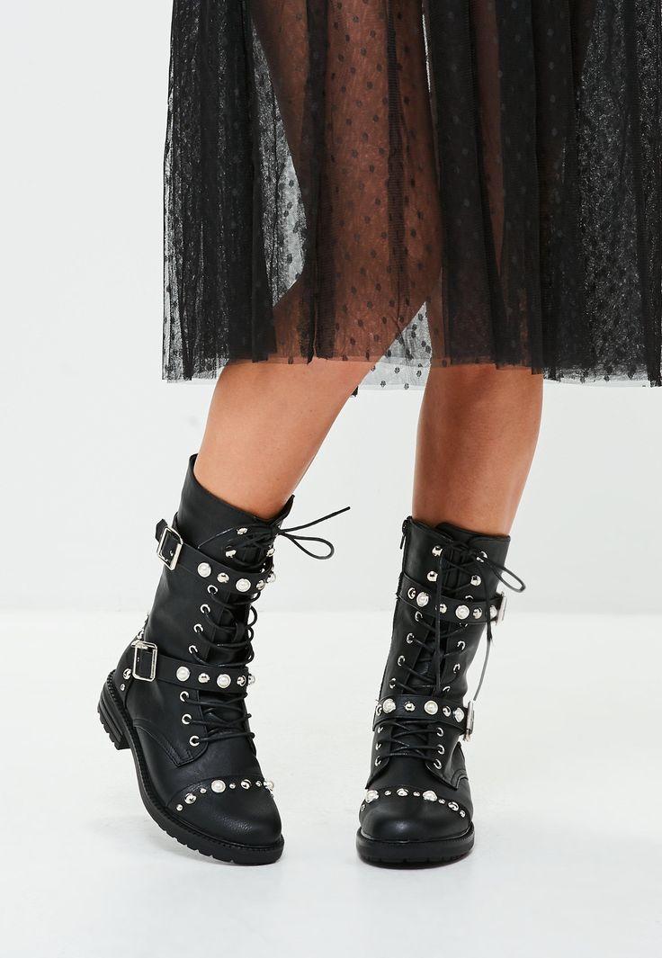 des bottines noires style militaire à clous contrastantes et perles. fermeture éclair sur le côté.