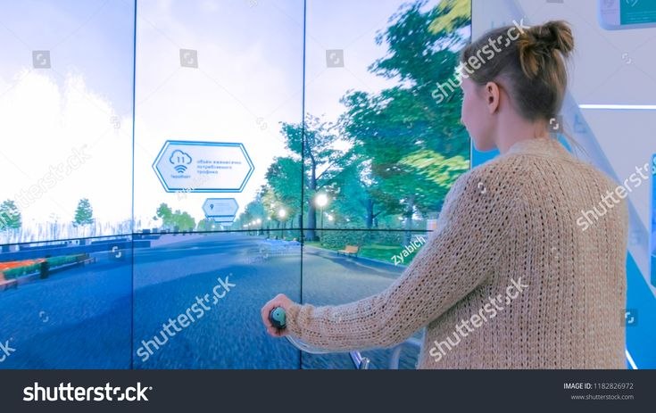 MOSCOW, RUSSIA – SEPTEMBER 10, 2017: Smart City Exhibition. Young woman using interactive bicycle simulator machine in front of large display at techn…