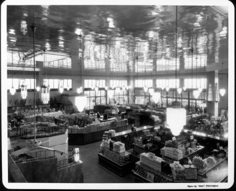 """The interior of a grocery store before it opens showing the merchandise in display cases and people looking in through the windows :: """"Dick"""" Whittington Photography Collection, 1924-1987"""