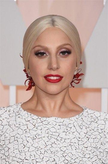Lady Gaga beauty look agli Oscar 2015Rossetto rosso intenso abbinato alla decorazione rossa del raccolto capelli di Lady Gaga tra i tagli capelli e beauty look delle star agli Oscar 2015.