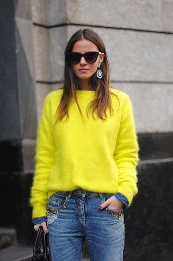 A neon fuzzy sweater looks so chic with a pair of distressed jeans and gem-encrusted statement earrings.     Image via The Glitter Guide