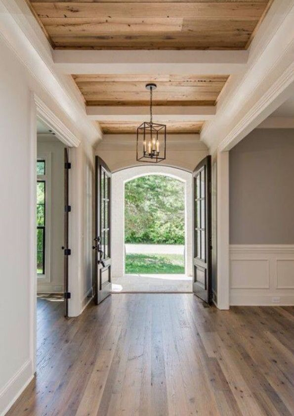 Mooie entree met openslaande deuren en houten plafonds